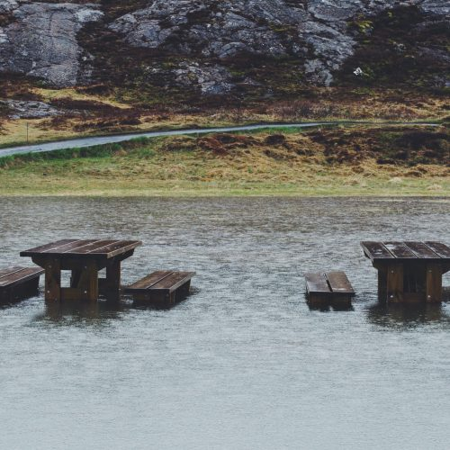 A pair of picnic tables, side by side, are nearly submerged in flood waters. Behind them, grey rock hills loom over a grassy, mossy landscape, greens and browns.