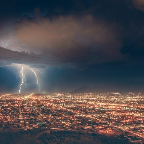 A pair of lightning bolts shoot down into a city aglow with electric lights. The nighttime sky is tinged with blue, dense with storm clouds.